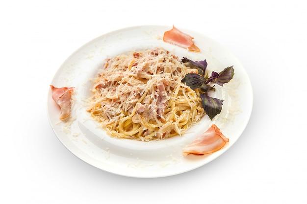 Spaghetti à la carbonara dans une sauce crémeuse saupoudrée de parmesan. assiette blanche avec des pâtes savoureuses et aromatiques sur une plaque blanche, isolée