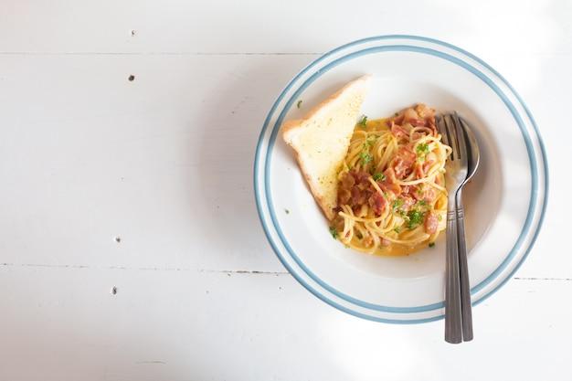 Spaghetti carbonara avec jambon, fromage et pain sur une table blanche