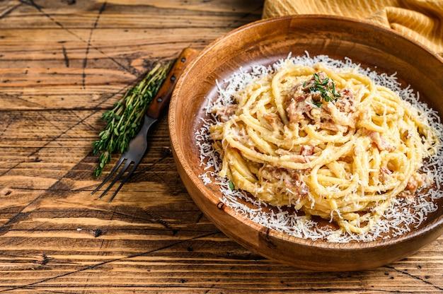 Spaghetti carbonara avec pancetta, œuf, fromage parmesan à pâte dure et sauce à la crème. table en bois. vue de dessus.