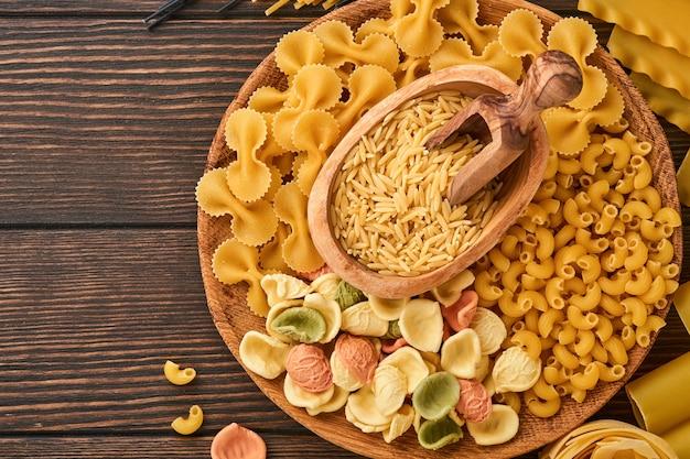 Spaghetti colorés, tagliatelles, farfalle, penne, ptititm, nouilles, fusilli, cannelloni sur un vieux fond en bois