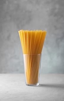 Spaghetti cru dans un verre. pâtes italiennes sèches préparées à partir de blé dur