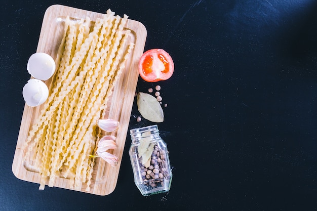 Spaghetti cru sur fond de bois noir, vue de dessus