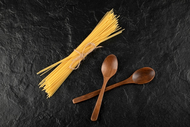 Spaghetti crus et cuillères en bois sur une surface noire