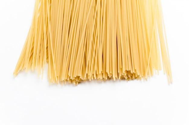 Spaghetti crus sur fond blanc.