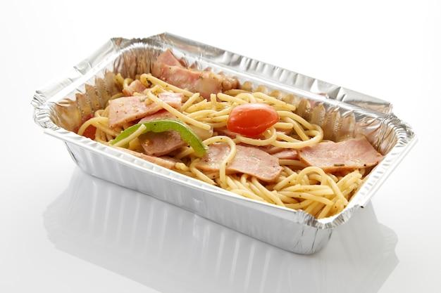 Spaghetti dans la livraison de nourriture de boîte d'aluminium sur fond blanc de table