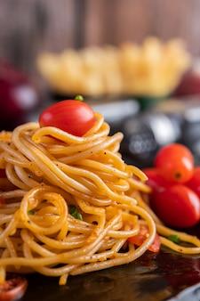 Spaghetti dans une tasse noire avec tomates et laitue.