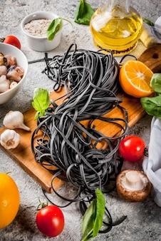 Spaghetti à l'encre de seiche noire non cuite crue avec des ingrédients pour cuisiner le dîner