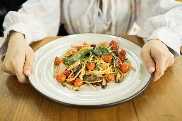 Spaghetti épicé avec bacon et basilic garni de fromage râpé dans le plat blanc.