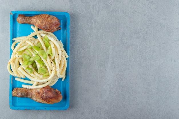 Spaghetti épicé et cuisses de poulet sur plaque bleue.