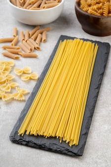 Spaghetti, farfalle, fusilli et pâtes penne sur un comptoir en béton.