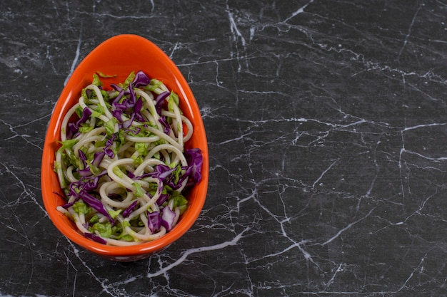 Spaghetti fraîchement préparé avec sauce aux légumes dans un bol orange.
