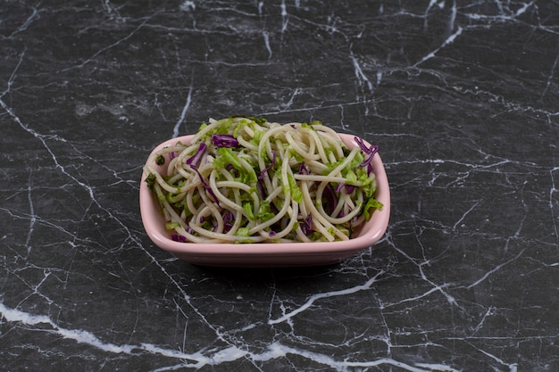 Spaghetti fraîchement préparé avec sauce aux légumes dans un bol rose.