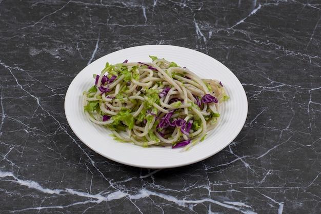 Spaghetti fraîchement préparé avec sauce aux légumes sur plaque blanche sur fond noir.