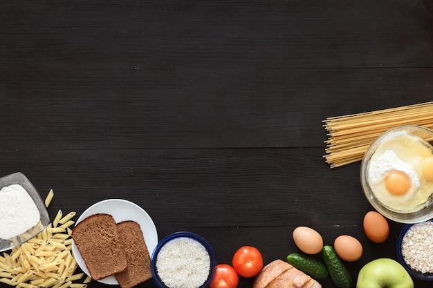 Spaghetti et légumes sur un bureau en bois noir