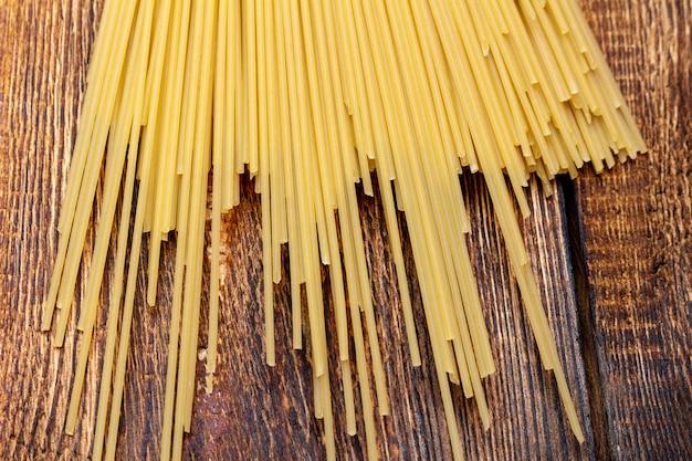 Spaghetti, macaroni, pâtes, linguine blé dur italien mince long sur fond de bois close up selective focus