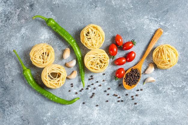 Spaghetti de nid non cuit aux légumes sur un fond de marbre