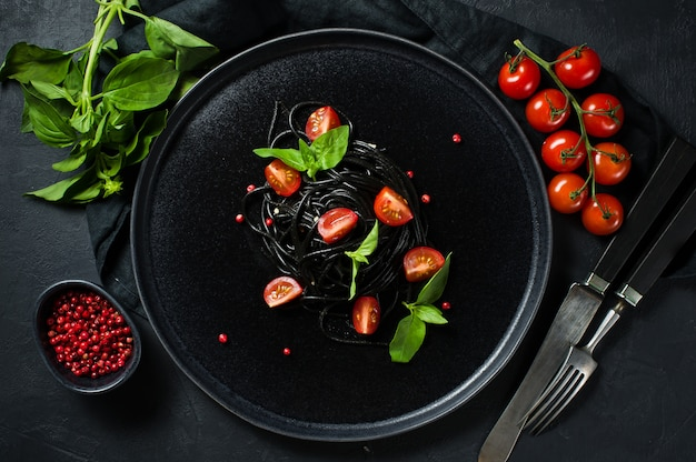 Spaghetti noir au basilic et tomates cerises, pâtes végétariennes.