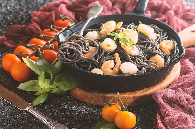 Spaghetti noir aux crevettes et pétoncles dans une poêle sur fond noir