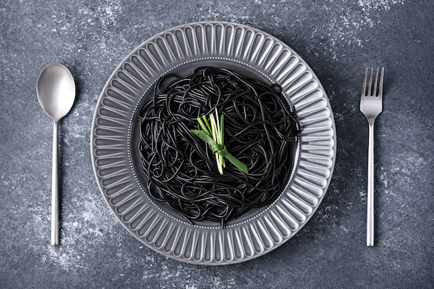 Spaghetti noir à l'encre de seiche sur plaque grise avec cuillère et fourchette sur fond gris, le temps de manger concept
