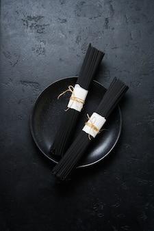 Spaghetti noir sur une vieille table en béton foncé. pâtes crues sèches à l'encre de seiche.