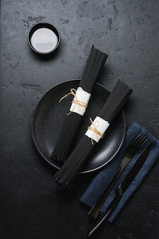 Spaghetti noir sur un vieux béton foncé. pâtes crues sèches à l'encre de seiche