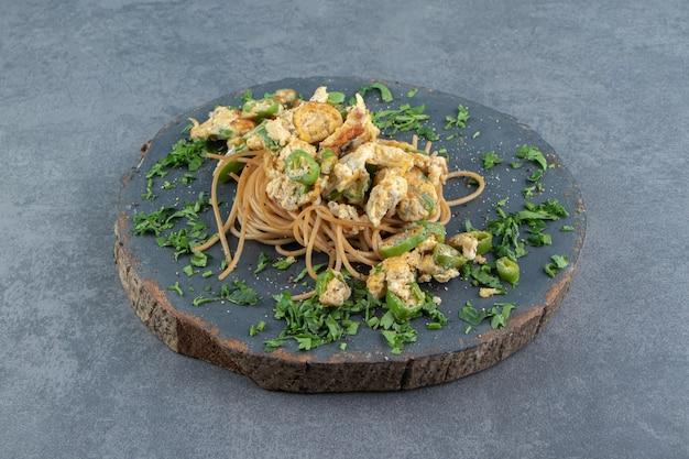 Spaghetti avec oeuf au plat sur morceau de bois.