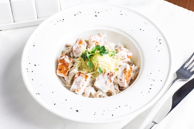 Spaghetti de pâtes au saumon, fromage et herbes en plaque blanche