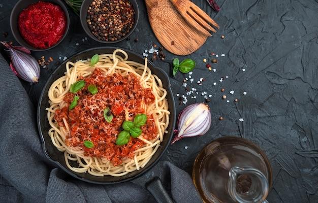 Spaghetti et pâtes à la bolognaise sur fond de béton noir.