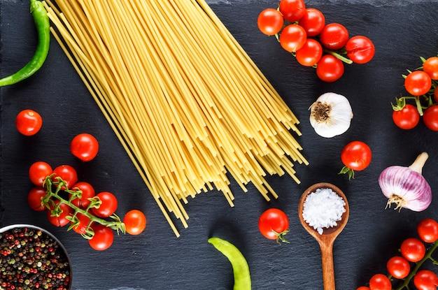 Spaghetti de pâtes sur fond noir, tomates cerises rouges