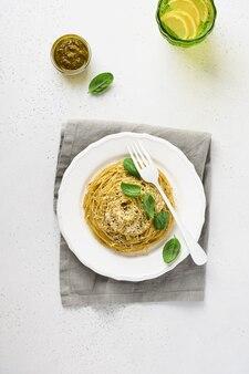 Spaghetti de pâtes avec sauce pesto et feuilles de basilic frais dans un bol blanc