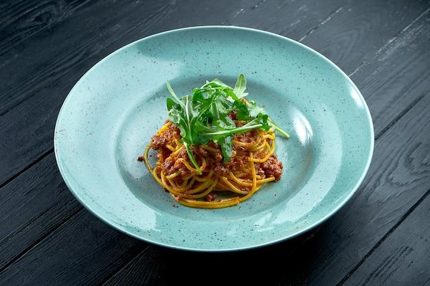 Spaghetti de pâtes traditionnelles à la viande hachée et sauce tomate bolognaise à la roquette, servi dans une assiette bleue sur fond noir en bois. cuisine italienne