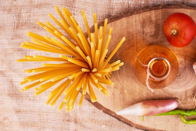 Spaghetti sur une planche de bois avec des ingrédients, vue du dessus.