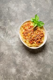 Spaghetti à la sauce bolognaise, parmesan râpé et brin de basilic sur fond gris