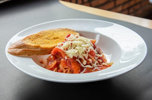 Spaghetti sauce tomate avec baguette et fromage sur plaque blanche