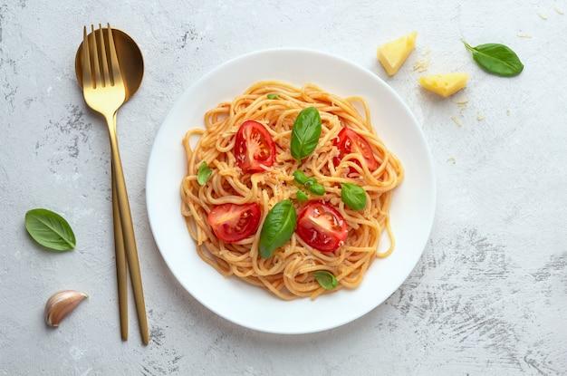 Spaghetti à la sauce tomate avec du fromage sur une plaque blanche sur un espace lumineux