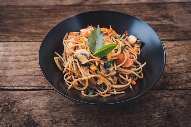 Spaghetti de saucisse épicée maison au basilic sur l'assiette sur la table en bois, style thaï