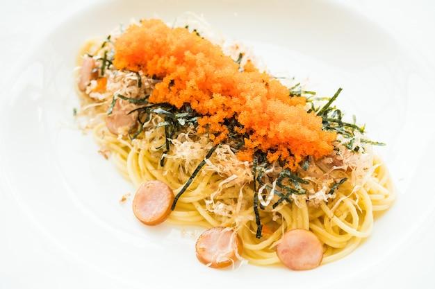 Spaghetti à la saucisse, œuf de crevette, algue, calmar sec sur le dessus
