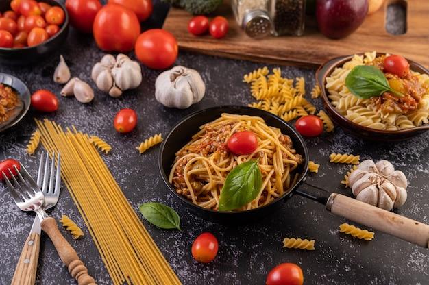 Spaghetti sautés dans une poêle avec tomates et basilic