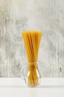 Spaghetti sec dans une mini cruche en verre vue latérale sur fond blanc et grunge