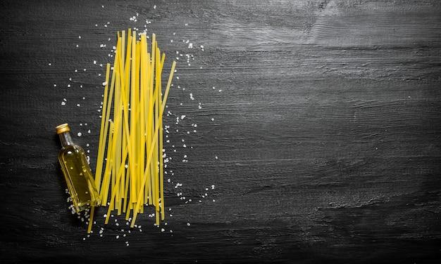 Spaghetti sec avec de l'huile d'olive et du sel sur un fond en bois noir
