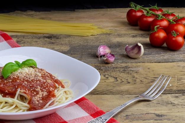 Spaghetti végétarien sur une table en bois, tomates, ail et pâtes en arrière-plan