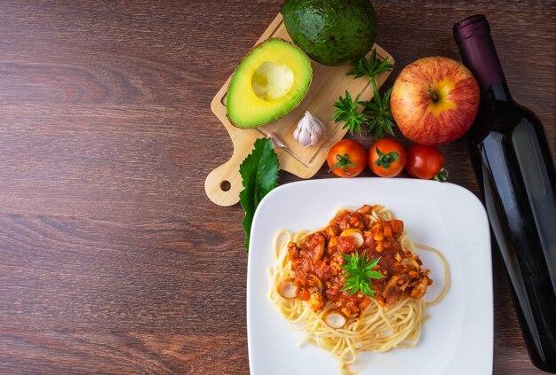 Spaghetti et vin rouge sur table en bois
