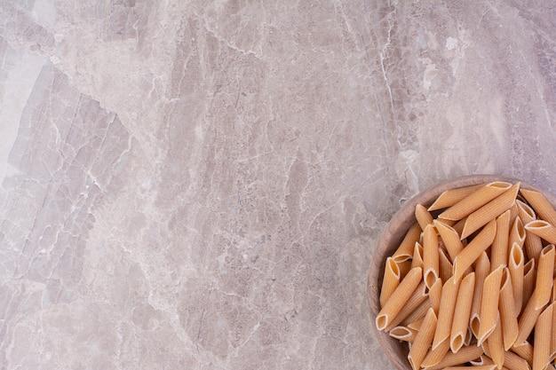 Spaghetties en forme de spirale dans une tasse en bois rustique sur le marbre