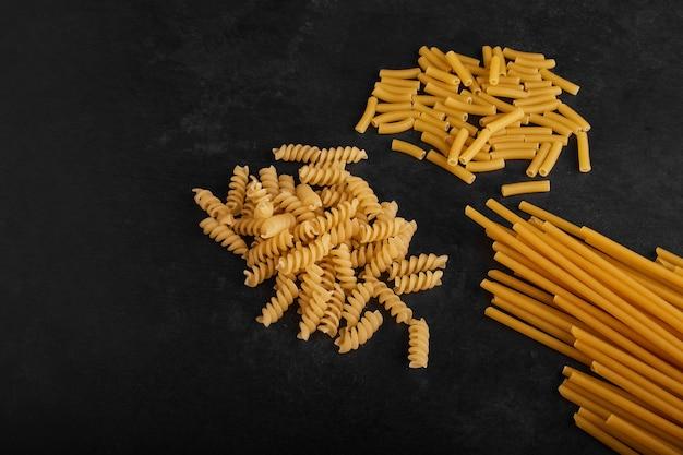 Spaghetties et pâtes sur surface noire.