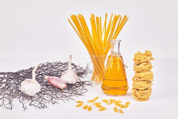 Spaghetties sur une surface blanche avec des ingrédients.