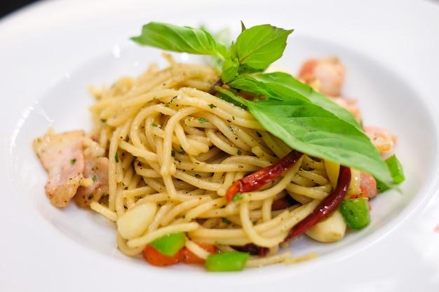 Les spaghettis au bacon épicé et au jambon au basilic pour le fond de la nourriture ou de la texture - nourriture faite maison