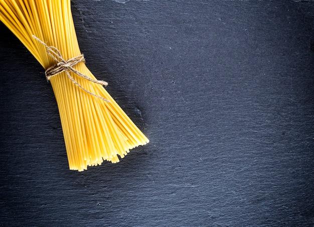 Spaghettis crus attachés avec une corde sur un fond noir