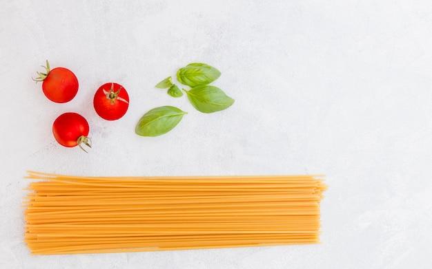 Spaghettis crus avec des feuilles de tomates et basilic sur fond texturé blanc