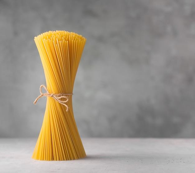 Spaghettis crus. pâtes italiennes sèches préparées à partir de blé dur, fond gris avec espace de copie