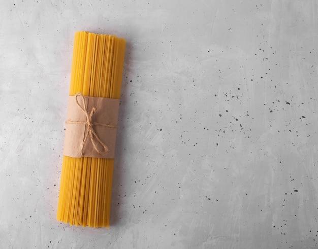 Spaghettis crus. pâtes italiennes sèches préparées à partir de blé dur, fond gris, vue de dessus avec espace de copie